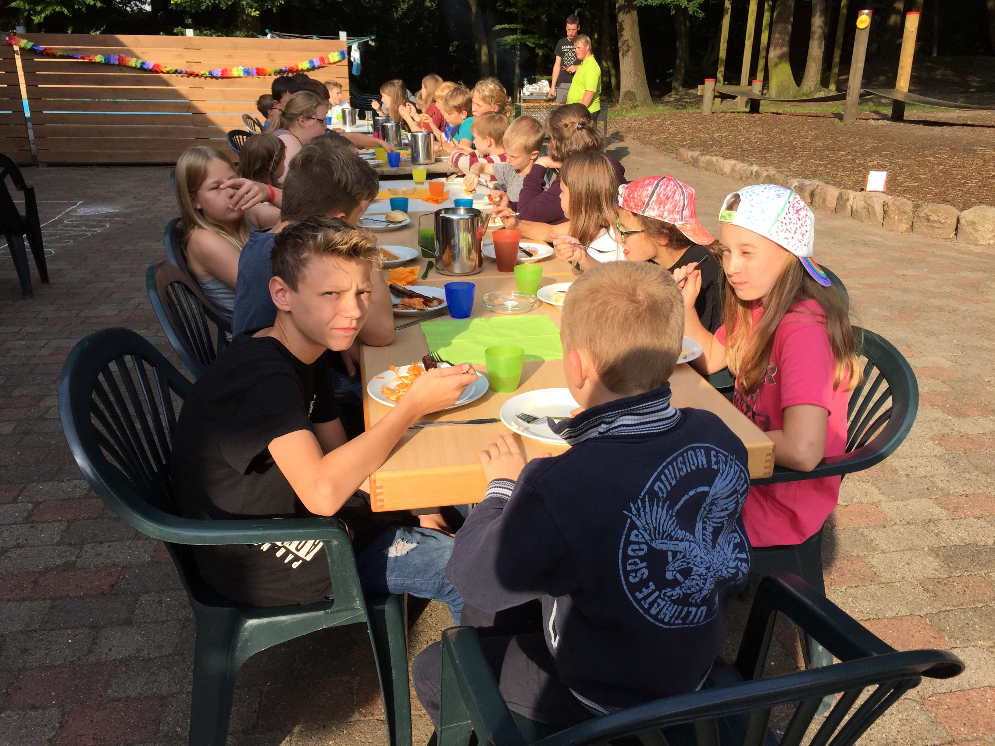 Die Kinder sittzen draußen an Tischen und essen.