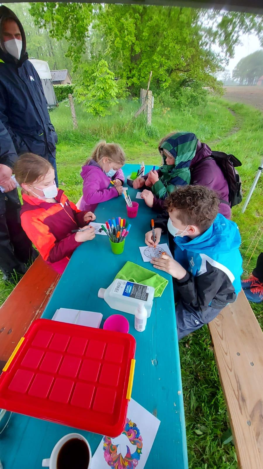 Kinder sitzen an einem Tisch und malen