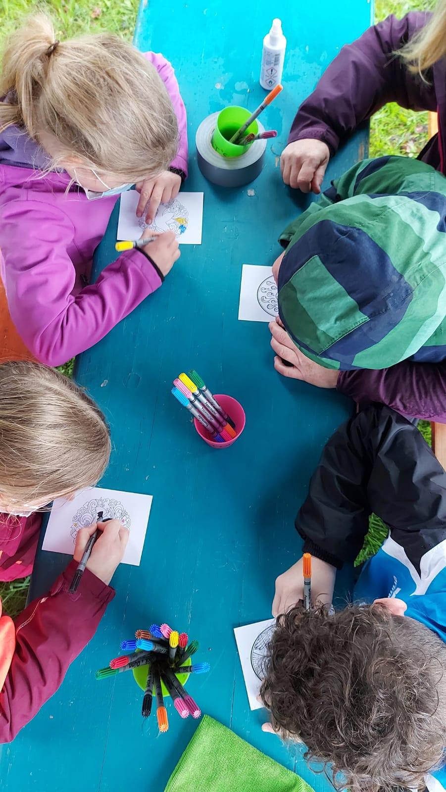 Blick von oben auf einen Tisch, an dem Kinder Bilder ausmalen